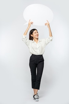 Uma jovem de camisa branca segurando um símbolo de caixa de pensamento