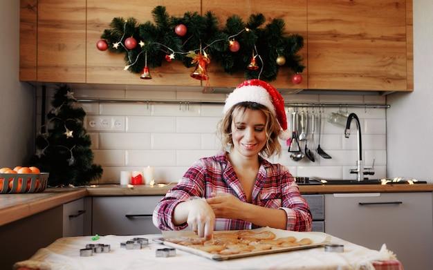 Uma jovem de camisa xadrez vermelha e chapéu vermelho prepara biscoitos de gengibre na cozinha para as celebrações do natal.