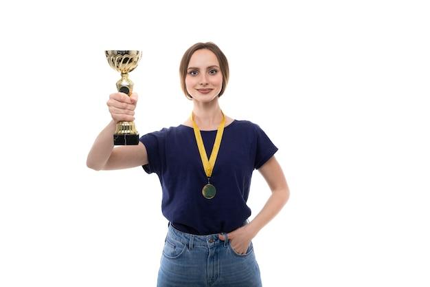 Uma jovem de camiseta e jeans segura uma taça de ouro