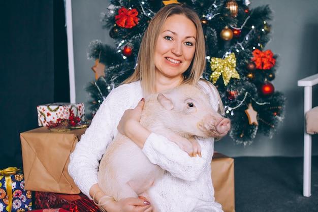 Uma jovem de camisola branca senta-se junto à árvore do ano novo com um porco nas mãos