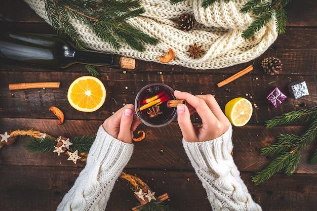 Uma jovem de camisola quente, tricotada e branca, está segurando um natal quente com vinho quente em um copo com especiarias e frutas cítricas. uma noite de inverno aconchegante. bebidas de inverno. vista plana leiga, superior.