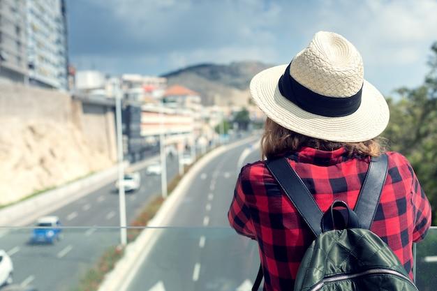 Uma jovem de chapéu com uma mochila fica em uma ponte de passeio e olha para a estrada