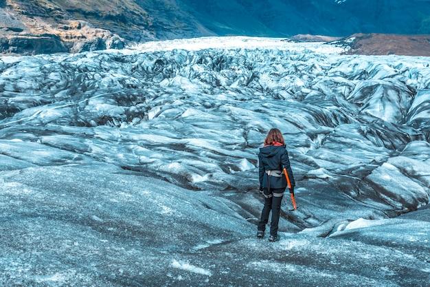 Uma jovem de costas, com botas e martelo, nas caminhadas na geleira de svinafellsjokull. islândia