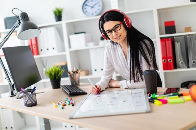 Uma jovem de fones de ouvido fica perto da mesa e desenha um marcador em um quadro magnético.