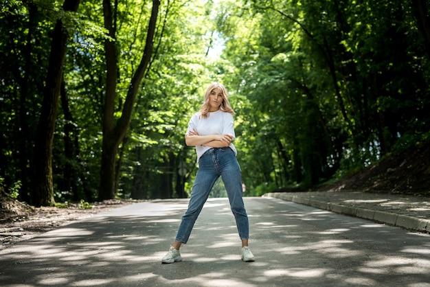 Uma jovem de jeans e camiseta branca se diverte muito na natureza na floresta. verão