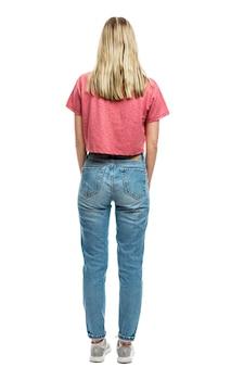 Uma jovem de jeans e camiseta vermelha está de pé. vista traseira. altura toda. isolado em uma parede branca vertical.