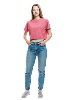 Uma jovem de jeans e camiseta vermelha fica de mãos dadas nos bolsos. altura toda. isolado em uma parede branca vertical.