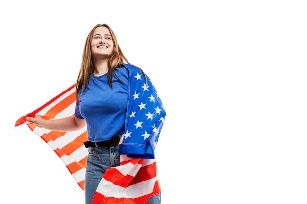 Uma jovem de jeans e uma blusa azul segura uma bandeira americana e ri. comemorando o dia da independência e o patriotismo. . espaço para texto.