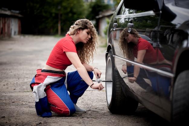 Uma jovem de macacão em uma garagem está consertando um automóvel.
