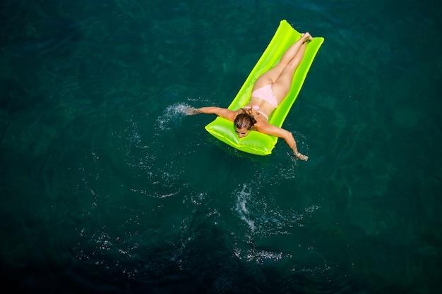 Uma jovem de maiô nada em um colchão inflável brilhante no mar. conceito de férias de verão.