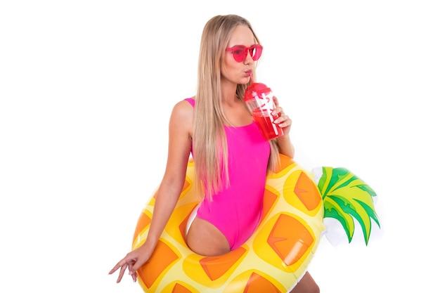 Uma jovem de maiô rosa e óculos segura uma roda inflável de natação e bebe limonada