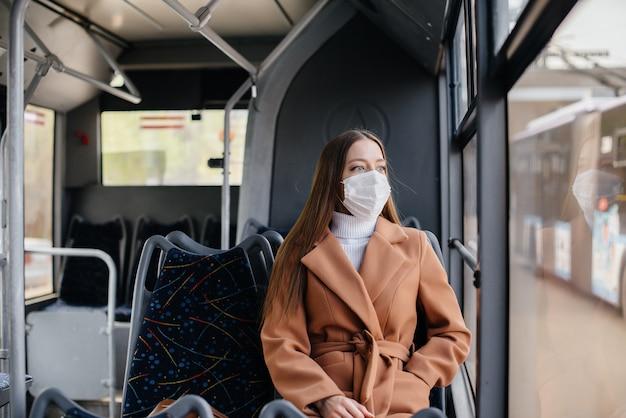 Uma jovem de máscara usa o transporte público sozinha, durante uma pandemia. proteção e prevenção covid-19.