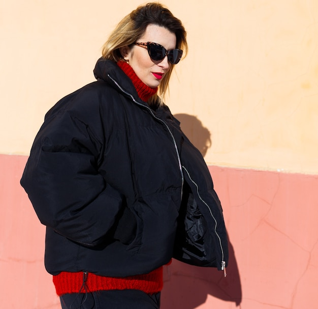 Uma jovem de óculos escuros, uma jaqueta preta e um suéter vermelho posa contra uma parede. hard light