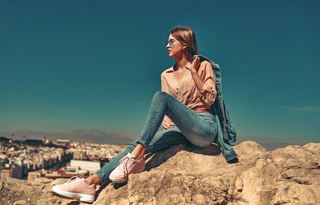 Uma jovem de óculos escuros, vestida de jeans e uma camisa senta-se em uma rocha, vista traseira da cidade costeira.