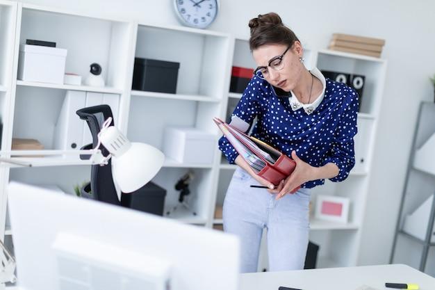 Uma jovem de óculos está de pé no escritório perto da mesa, falando ao telefone e segurando pastas com documentos.