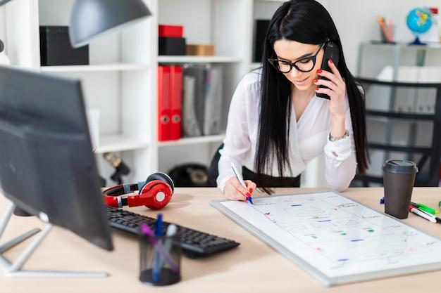 Uma jovem de óculos fica perto de uma mesa, fala ao telefone e desenha um marcador em um quadro magnético.