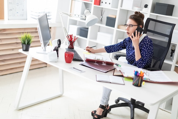 Uma jovem de óculos senta-se no escritório em uma mesa de computador e está falando ao telefone.