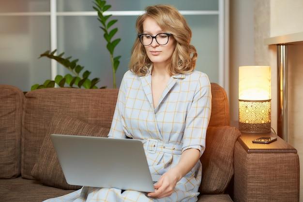 Uma jovem de óculos trabalha remotamente em um computador desktop em seu apartamento. uma senhora durante uma reunião de negócios em vídeo em casa. Foto Premium