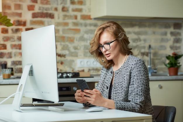 Uma jovem de óculos trabalha remotamente em um computador desktop em seu estúdio. uma chefe do sexo feminino usa um smartphone durante uma videoconferência em casa.