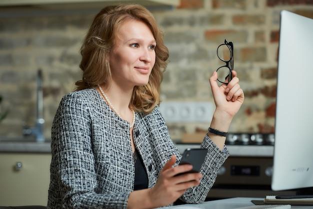 Uma jovem de óculos trabalha remotamente em um computador desktop em seu estúdio. uma senhora participando de uma videoconferência em casa.
