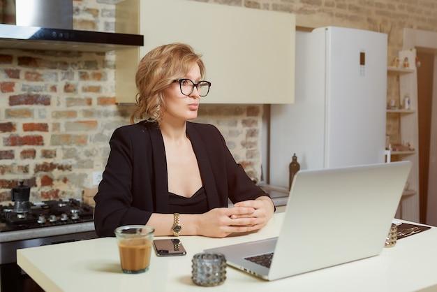 Uma jovem de óculos trabalha remotamente em um laptop em sua cozinha. uma garota com aparelho gesticulando enquanto conversava com seus colegas em uma videoconferência em casa.