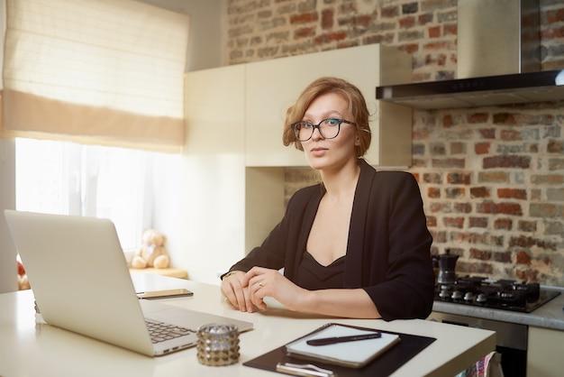 Uma jovem de óculos trabalha remotamente em um laptop em sua cozinha. uma loira ouvindo seus colegas em uma videoconferência em casa. uma senhora que estuda uma lição on-line em um webinar.