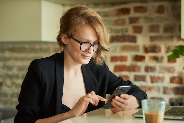 Uma jovem de óculos trabalhando remotamente em um café. uma senhora loira usando um smartphone em casa. uma professora que procura informações no celular.