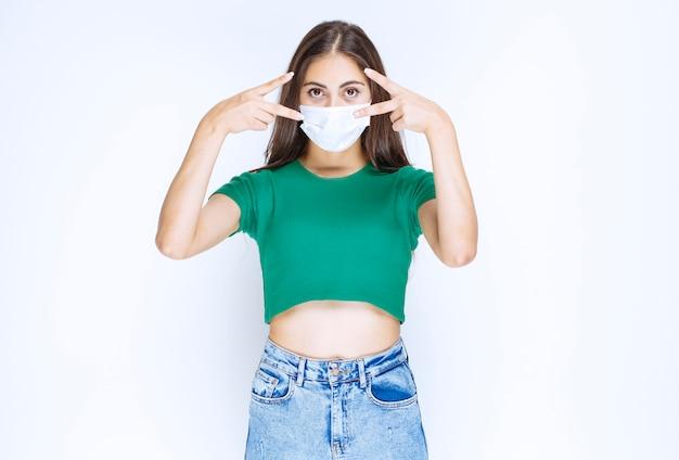 Uma jovem de pé na máscara médica protetora e mostrando sinal de vitória.