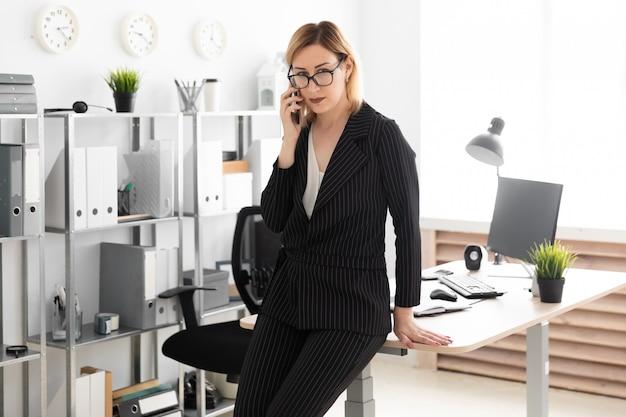 Uma jovem de pé no escritório e falando ao telefone.