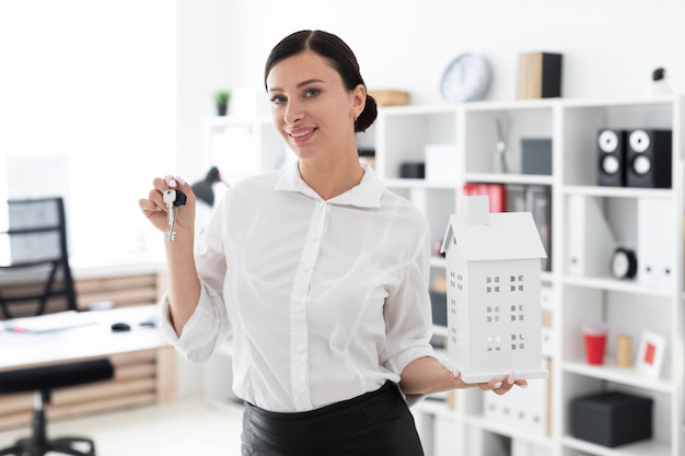 Uma jovem de pé no escritório e segurando as chaves e o layout da casa.