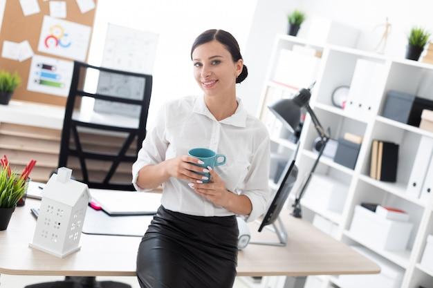 Uma jovem de pé no escritório e segurando uma xícara.
