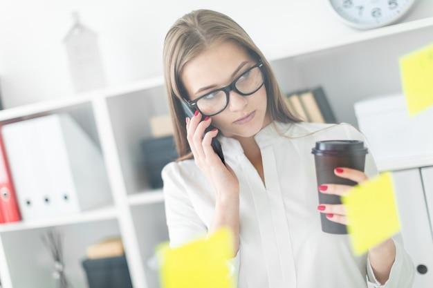 Uma jovem de pé perto da placa com adesivos no escritório. nas mãos da menina um copo de café e telefone