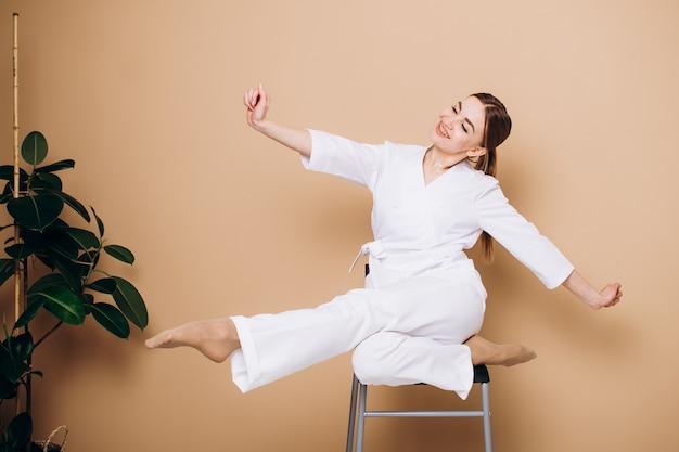 Uma jovem de quimono branco se senta em uma cadeira e faz exercícios ou ioga em casa