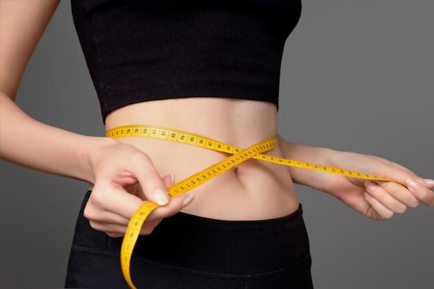 Uma jovem de sportswear preto mede a cintura com um centímetro sobre um fundo cinza escuro, cintura fina. corpo atlético saudável, dieta, perda de peso, contagem de calorias. conceito de emagrecimento