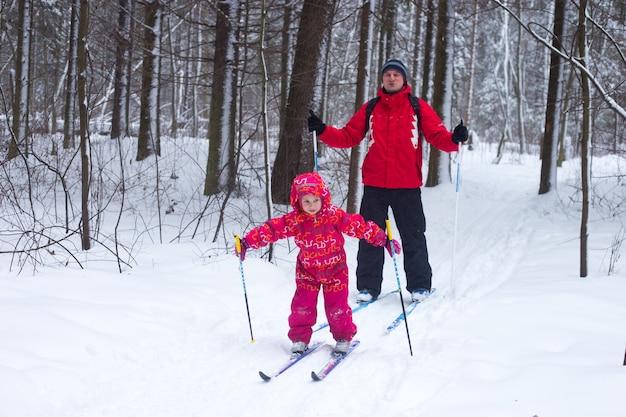 Uma jovem de terno vermelho está aprendendo a esquiar