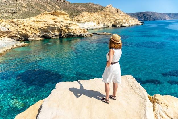 Uma jovem de vestido branco olhando o mar em rodalquilar em cabo de gata em um lindo dia de verão, almería