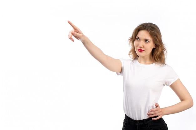 Uma jovem de vista frontal em camisa branca e calça jeans preta moderna, apontando para a distância em branco
