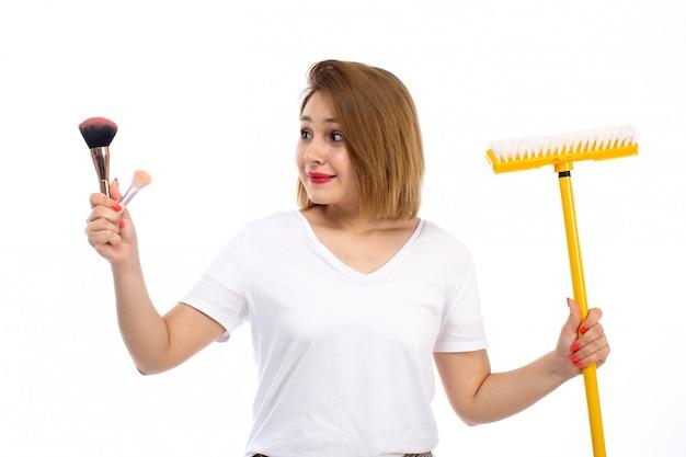 Uma jovem de vista frontal em camisa branca e calças modernas leves segurando coisas de esfregão e maquiagem amarelas no branco