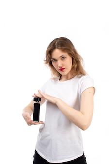 Uma jovem de vista frontal em shorts de camiseta branca preta segurando o tubo preto no branco