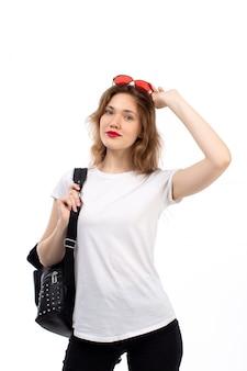 Uma jovem de vista frontal em t-shirt branca, óculos de sol vermelho, bolsa preta, sorrindo no branco