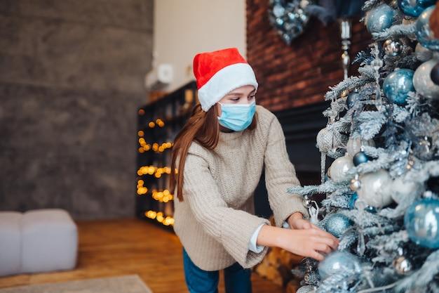 Uma jovem decora a árvore de natal com máscaras médicas