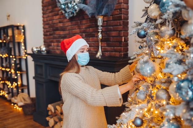 Uma jovem decora a árvore de natal com uma máscara médica