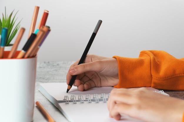 Uma jovem desenha no álbum com um lápis preto. mão de perto.