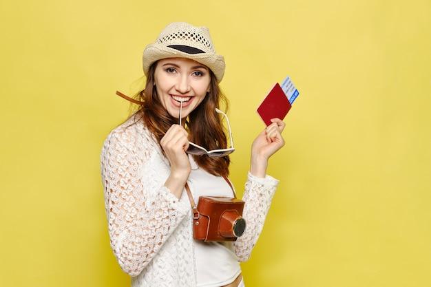 Uma jovem detém um bilhete com um passaporte e uma câmera em um fundo amarelo