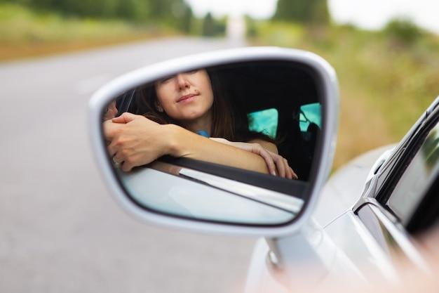 Uma jovem dirigindo um carro, a garota se olha no espelho lateral. entrega pelo direito de dirigir automóvel.