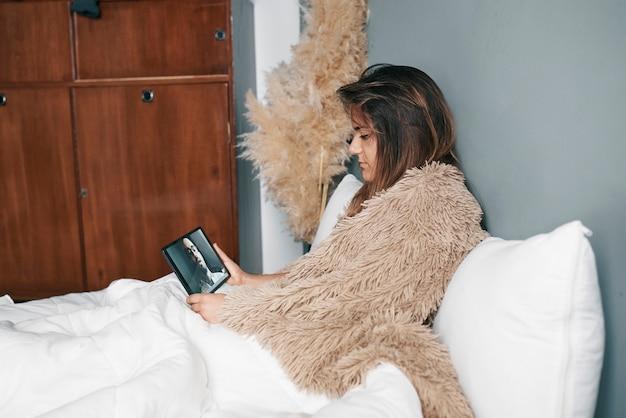 Uma jovem doente na cama faz uma videochamada com um tablet para o médico