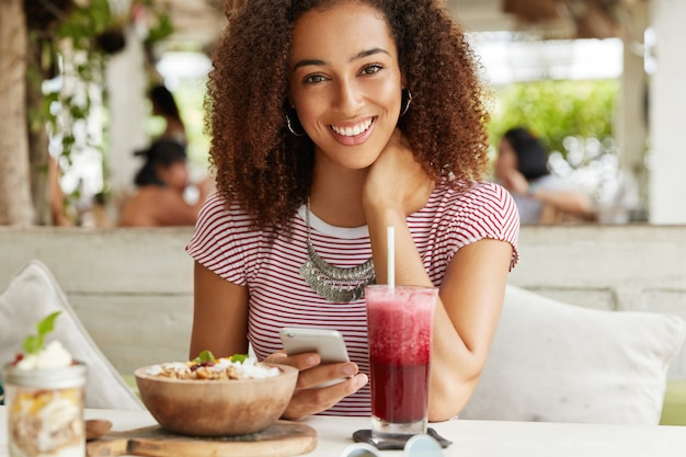 Uma jovem e adorável freelancer afro-americana faz configurações no celular, bebe smoothie e uma salada doce exótica, passa o tempo livre em um café ao ar livre, tem uma expressão positiva e um sorriso