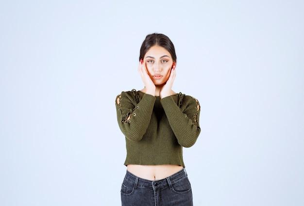 Uma jovem e adorável modelo segurando seu rosto e posando