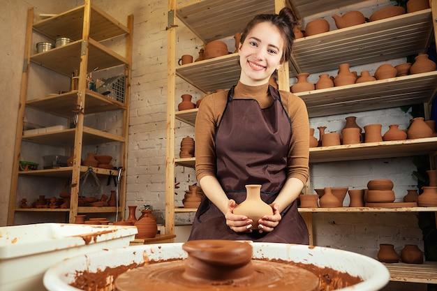 Uma jovem e alegre esculpe em argila. o oleiro trabalha em uma oficina de olaria com barro. o conceito de maestria e criatividade em cerâmica.
