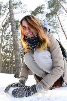 Uma jovem e alegre menina caucasiana em um casaco marrom esculpe a neve